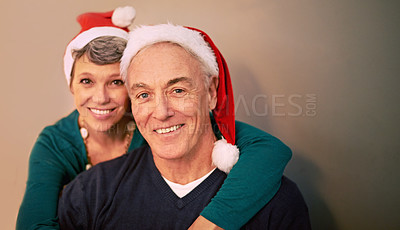 Buy stock photo Portrait of a happy mature couple wearing santa hats at Christmastime