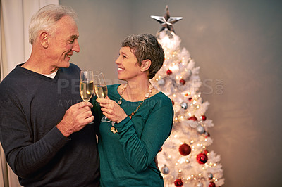 Buy stock photo Cropped shot of a happy mature couple toasting each other on Christmas eve