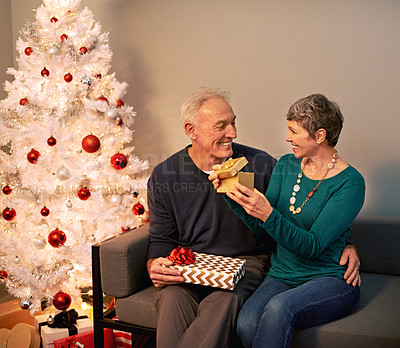 Buy stock photo Shot of a happy mature couple exchanging gifts on Christmas eve