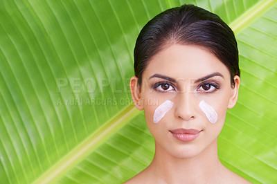 Buy stock photo Studio portrait of a beautiful young woman with moisturizer on her face posing in front of a leaf