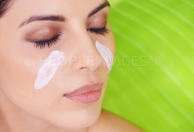 Buy stock photo Studio shot of a beautiful young woman with moisturizer on her face posing against a green leaf