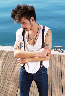 Buy stock photo A young man showing off his tattoos outdoors