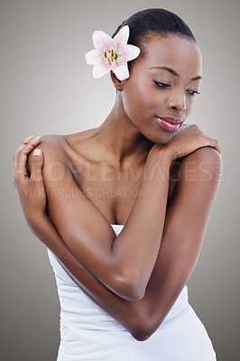 Buy stock photo Studio portrait of a beautiful african american model with an orchid against a gray background