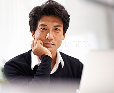 Buy stock photo A handsome asian businessman working on his laptop in the office