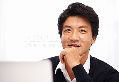 Buy stock photo Portrait of a handsome asian businessman working on his laptop in the office