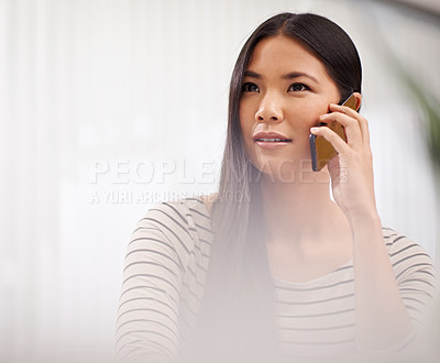 Buy stock photo Shot of a young businesswoman talking on the phone while sitting at her desk