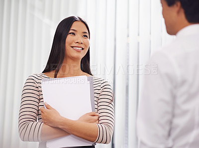 Buy stock photo Shot of a young asian businesswoman holding documents speaking to a colleague