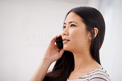Buy stock photo An attractive young asian woman using her mobile phone while indoors