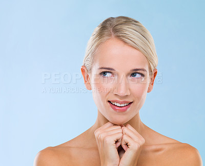 Buy stock photo Studio shot of a beautiful blonde looking awayagainst a blue background