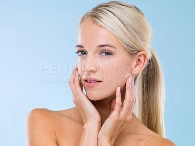 Buy stock photo Studio shot of a beautiful blonde touching her face against a blue background