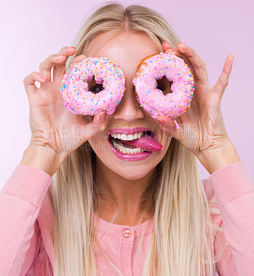Buy stock photo Cropped shot of a woman holding donuts in front of her eyes while isolated on pink