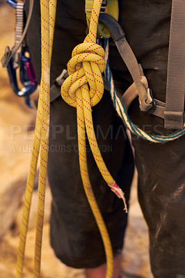 Buy stock photo Cropped shot of a young rock climber standing and adjusting his harnesses