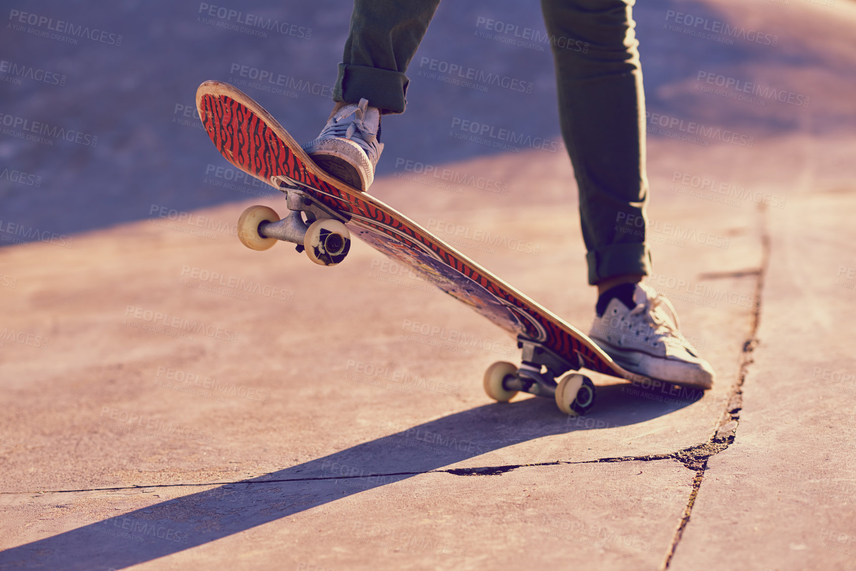 Buy stock photo A cropped shot of a woman doing a trick on a skateboard