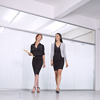 Buy stock photo Two colleagues walking together in the office talking