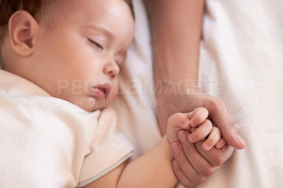 Buy stock photo A baby girl sleeping while holding her mother's hand