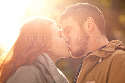 Buy stock photo Shot of a happy young couple sharing a kiss outdoors