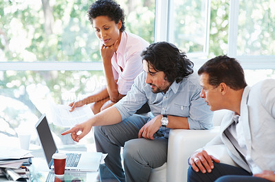 Buy stock photo Business man points something out to his colleagues on laptop