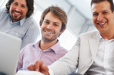 Buy stock photo Three business people smiling while using laptop at office