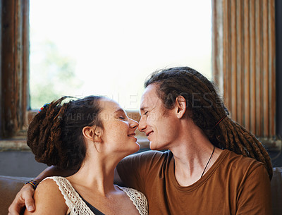 Buy stock photo Shot of an affectionate dread-locked couple sitting at home