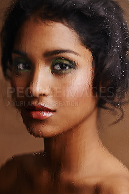 Buy stock photo Shot of a beautiful indian woman through a blurred wet window