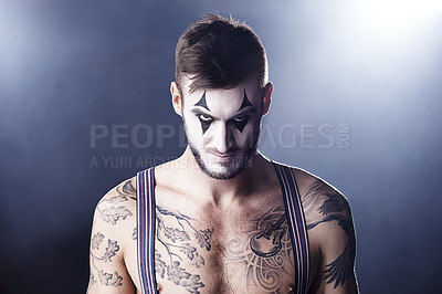 Buy stock photo Studio shot of a tattooed man with clown makeup on