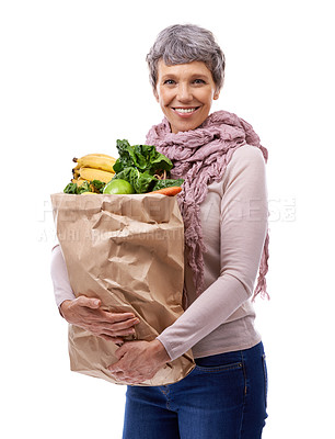 Buy stock photo Studio portrait of a mature woman holding a brown paper bag filled with fruit and vegetables
