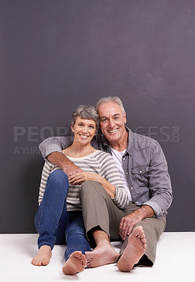 Buy stock photo A happy senior couple sitting together and smiling in the studio