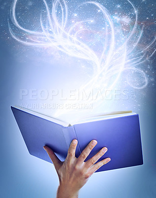 Buy stock photo Shot of a hand holding an open storybook with light emanating from it