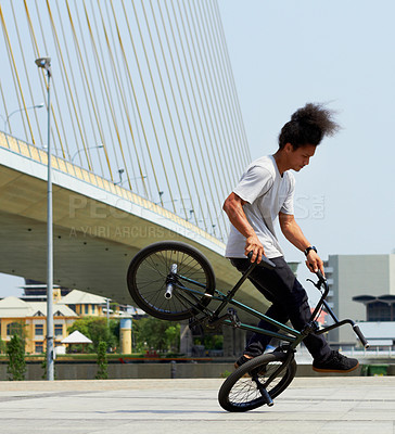 Buy stock photo A young bmx rider doing tricks out in the city