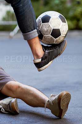 Buy stock photo Shot of a young people playing football in the street