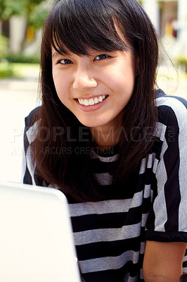 Buy stock photo Portrait of an attractive young female student using her laptop on campus
