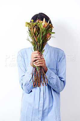 Buy stock photo Studio shot of an attractive young ethnic woman holding a bouquet of flowers in front of her face