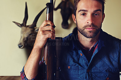 Buy stock photo Portrait of a hunter standing in front of his trophies