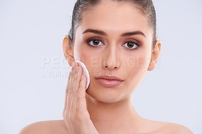 Buy stock photo Studio portrait of a beautiful young woman cleansing her face with a cotton pad