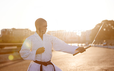 Buy stock photo A young karate professional practicing while wearing a gi