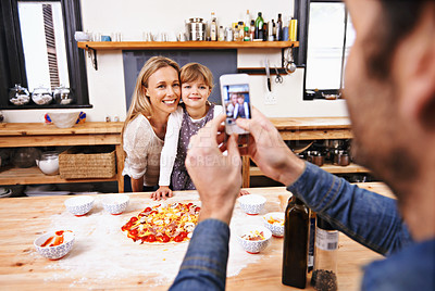 Buy stock photo A dad taking a photo of his family making homemade pizza