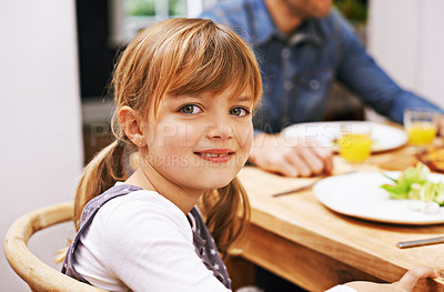 Buy stock photo A little girl sitting at the dinner table