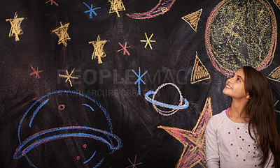 Buy stock photo Shot of a little girl standing in front of a chalkboard drawing