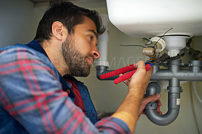 Buy stock photo Shot of a plumber fixing a pipe