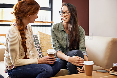 Buy stock photo Cropped shot of two young women sitting in a coffee shop