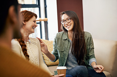 Buy stock photo Cropped shot of three young friends sitting in a coffee shop