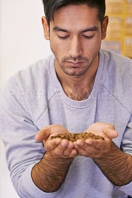 Buy stock photo Shot of a young man holding raw coffee beans
