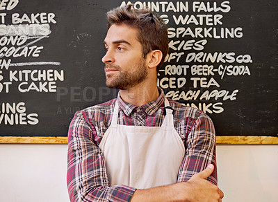 Buy stock photo Shot of a barista standing in front of a menu written on a blackboard