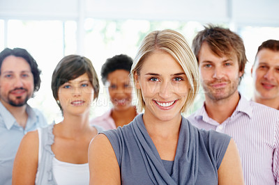 Buy stock photo Attractive business woman smiling with colleagues in background