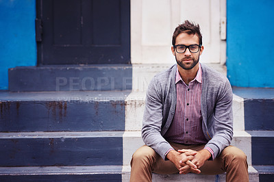 Buy stock photo Shot of a handsome young man sitting on steps