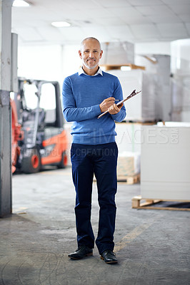 Buy stock photo A manager standing on the factory floor with a clipboard and a smile