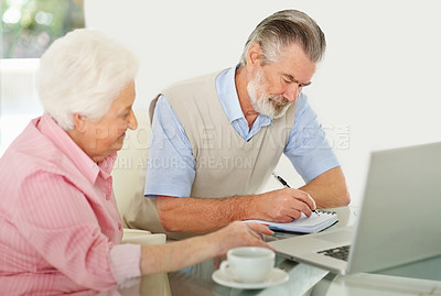 Buy stock photo Shot of an elderly couple doing their home finances in front of a laptop