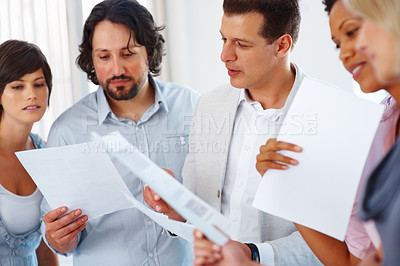 Buy stock photo Successful young people looking at business plan in office