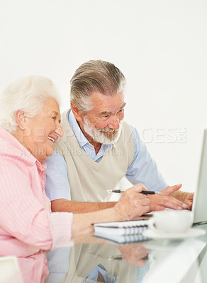 Buy stock photo Portrait of a happy senior couple working on laptop at home