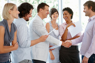 Buy stock photo Two Business men shaking hands while team smiling at office